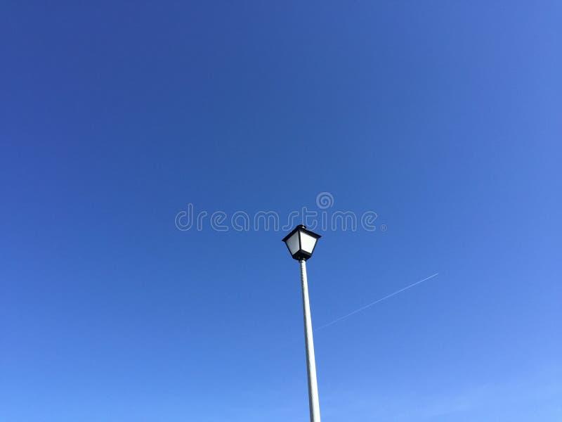 Duidelijke blauwe hemel met lightpost en het overgaan van vliegtuig royalty-vrije stock foto's