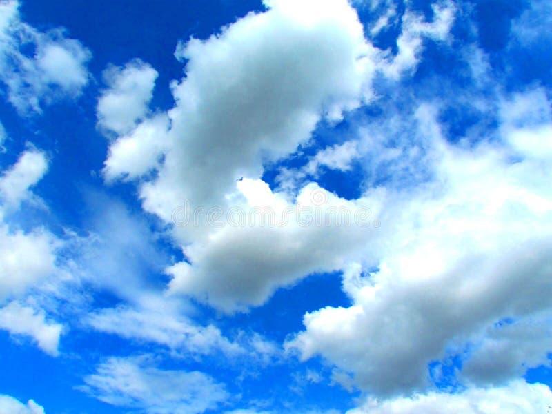 Duidelijke blauwe hemel met pluizige wolken stock afbeeldingen