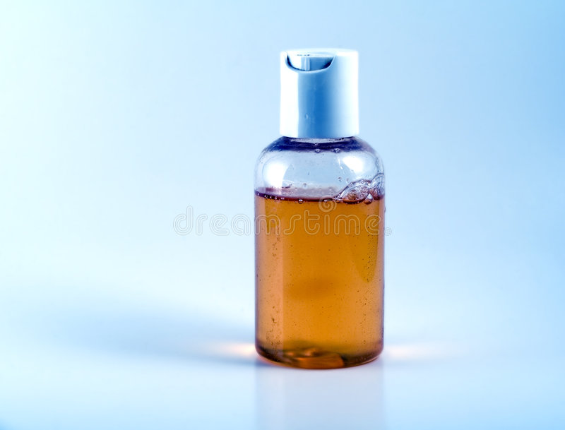 Duidelijke fles met ambervloeistof stock afbeeldingen
