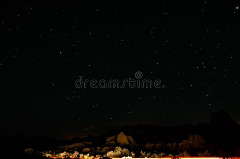 Duidelijke nachthemel met sterren en auto's stock foto's