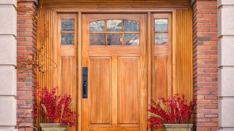 Duidelijke Panorama Bruine houten voordeur met decoratieve glaspanelen bij de ingang van een huis stock foto's