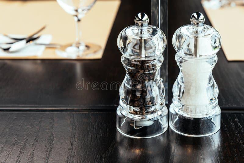 Duidelijke plastic Peper en Zoute molens op houten lijst voor voedselkruiden met exemplaarruimte stock afbeelding