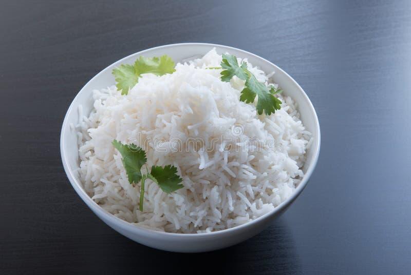 Duidelijke rijst in ovale messingskom over zwarte achtergrond royalty-vrije stock afbeelding