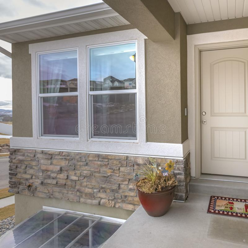 Duidelijke Vierkante Witte voordeur en weerspiegelend venster van een huis tegen weg en bewolkte hemel stock afbeeldingen
