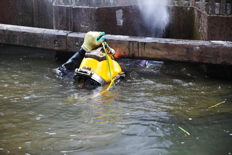 Duiker met gele helm die in vuil water bij kustrei werken royalty-vrije stock fotografie