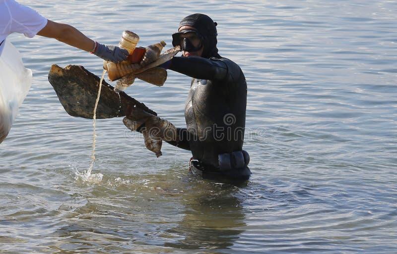 Duikers die tijdens milieu het schoonmaken stranddag plastiek verwijderen stock foto