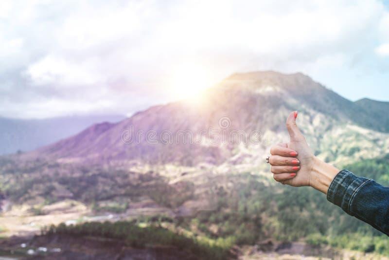 Duim omhoog op een mooie bergachtergrond met zonlicht Volcano Batur, het eiland van Bali royalty-vrije stock foto's