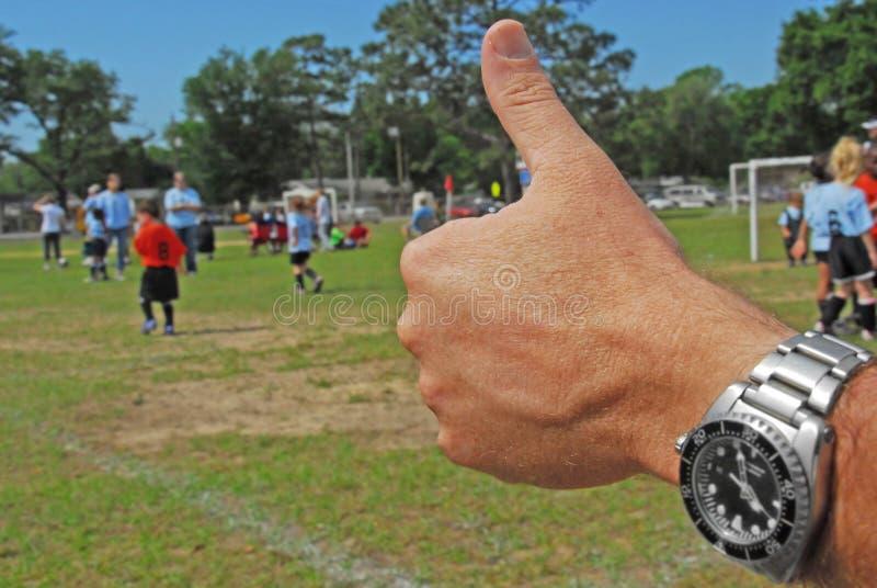 Duimen omhoog bij voetbalspel stock foto