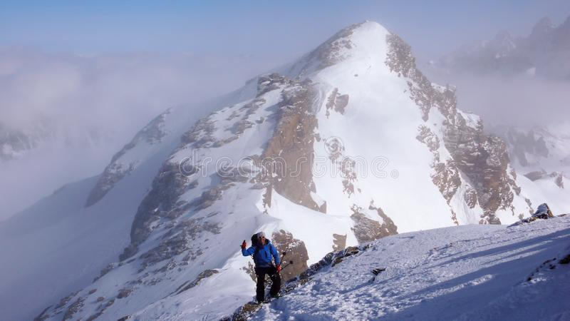 Duimen omhoog van een mannelijke backcountry skiër die aan een hoge alpiene top in Zwitserland langs een rots en sneeuwrand in li stock afbeelding
