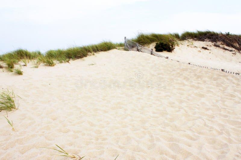 Duinen met gras tegen hemel - schuur bijna het begraven van omheining - Achtergrond - Zaal voor tekst royalty-vrije stock foto
