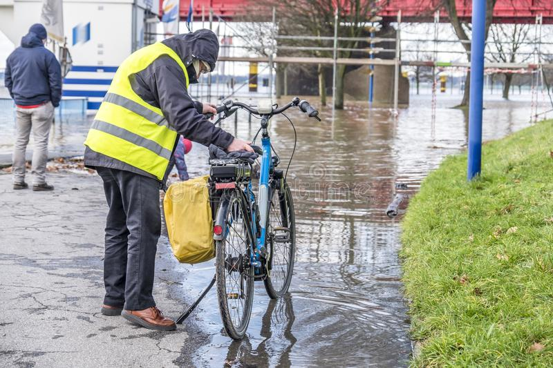 Duisburg , Germany - January 08 2017 : Bicycle driver surprised by the river Rhine flooding the promenade in Ruhrort. DUISBURG , GERMANY - JANUARY 08 2017 stock photo