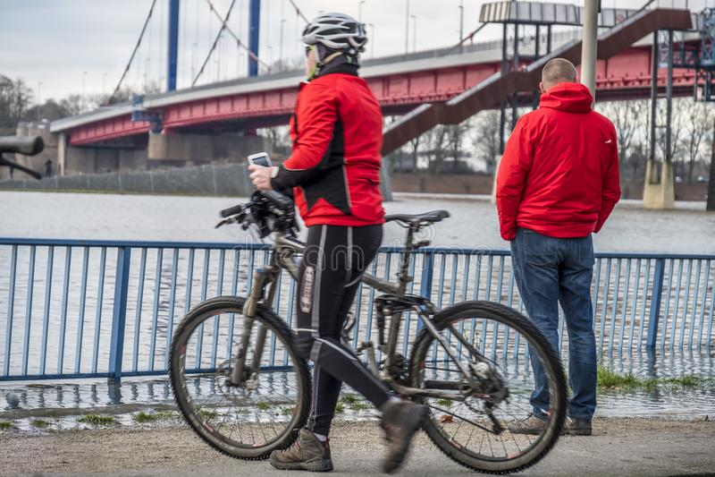 Duisburg , Germany - January 08 2017 : Bike driver surprised by the river Rhine flooding the promenade. In Ruhrort stock image