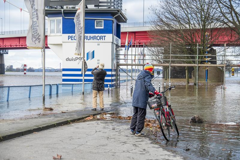 Duisburg , Germany - January 08 2017 : Lady surprised by the river Rhine flooding the promenade. In Ruhrort stock photos