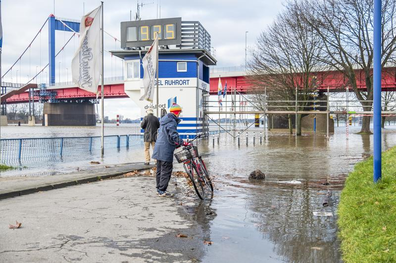 Duisburg , Germany - January 08 2017 : Lady surprised by the river Rhine flooding the promenade. In Ruhrort stock photography
