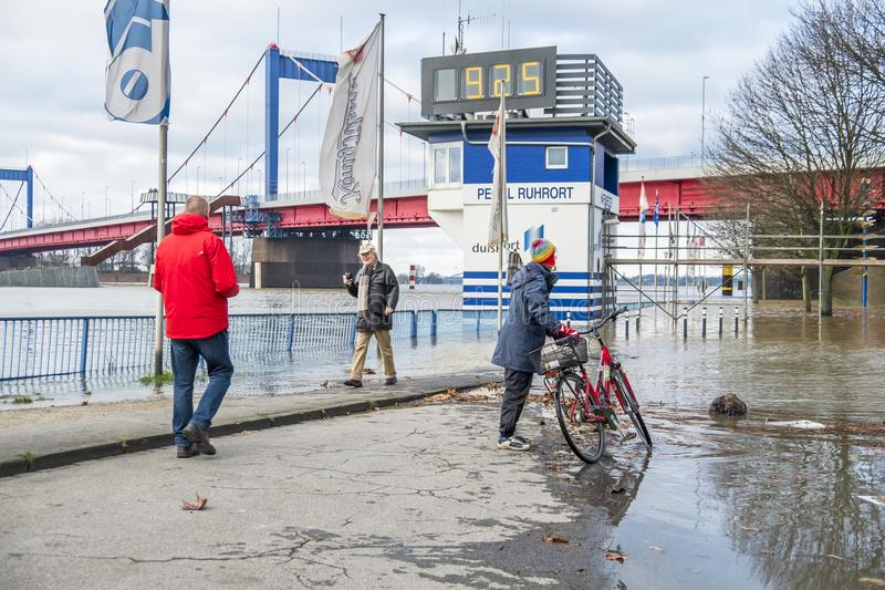 Duisburg , Germany - January 08 2017 : Lady surprised by the river Rhine flooding the promenade. In Ruhrort royalty free stock photos