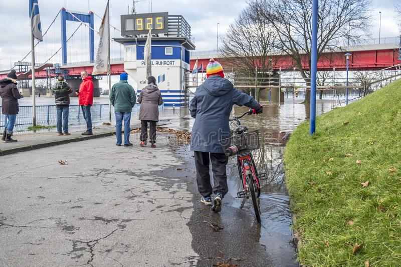 Duisburg , Germany - January 08 2017 : Lady surprised by the river Rhine flooding the promenade in Ruhrort. DUISBURG , GERMANY - JANUARY 08 2017 : Lady surprised royalty free stock photo