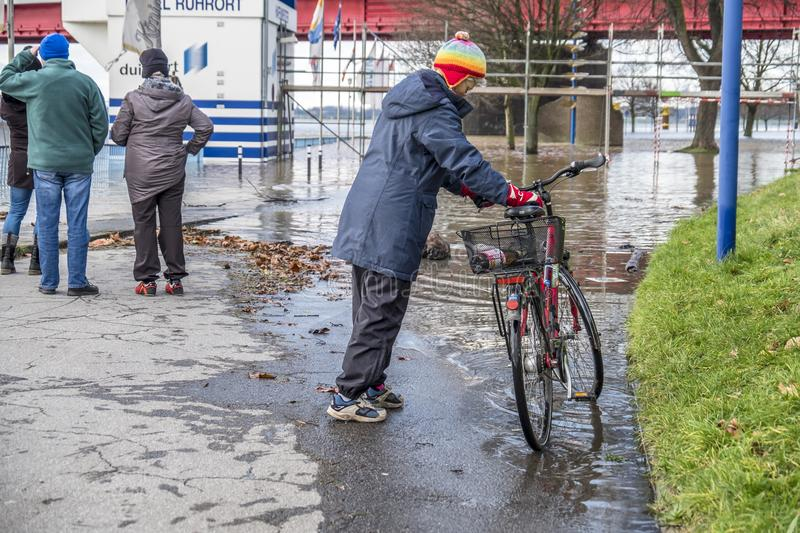 Duisburg , Germany - January 08 2017 : Lady surprised by the river Rhine flooding the promenade in Ruhrort. DUISBURG , GERMANY - JANUARY 08 2017 : Lady surprised royalty free stock images