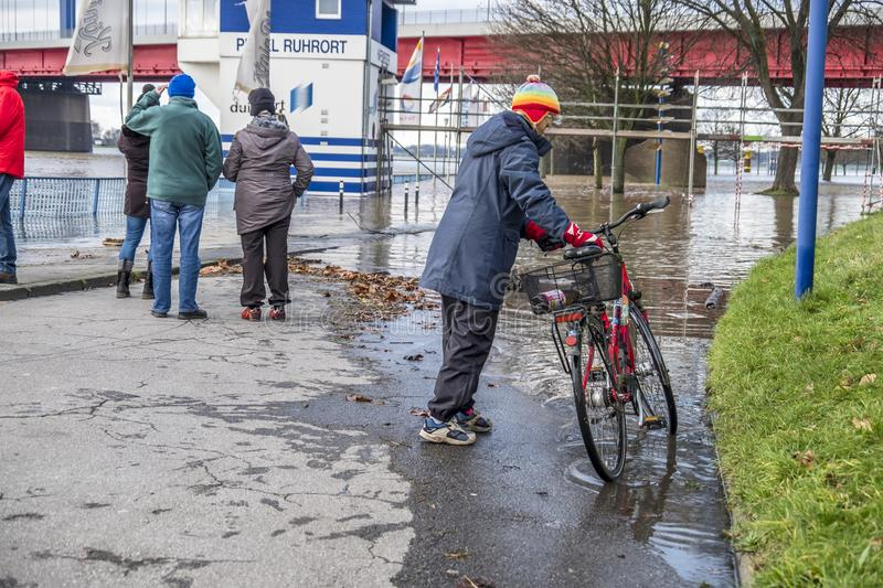 Duisburg , Germany - January 08 2017 : Lady surprised by the river Rhine flooding the promenade in Ruhrort. DUISBURG , GERMANY - JANUARY 08 2017 : Lady surprised stock images