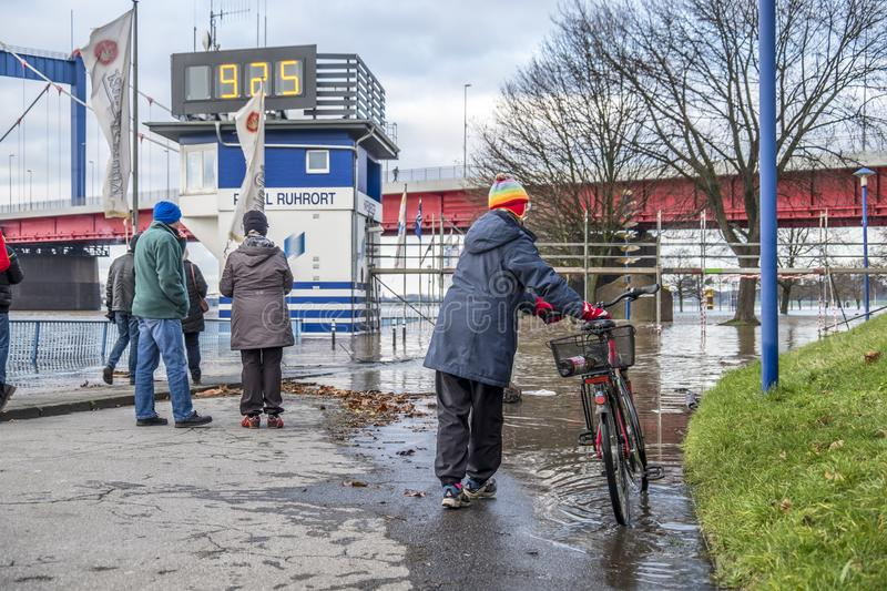 Duisburg , Germany - January 08 2017 : Lady surprised by the river Rhine flooding the promenade in Ruhrort. DUISBURG , GERMANY - JANUARY 08 2017 : Lady surprised royalty free stock image