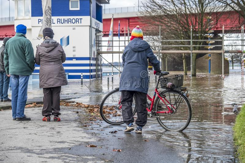 Duisburg , Germany - January 08 2017 : Lady surprised by the river Rhine flooding the promenade in Ruhrort. DUISBURG , GERMANY - JANUARY 08 2017 : Lady surprised royalty free stock photos