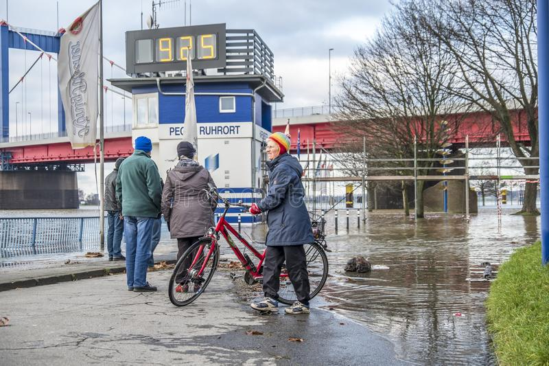 Duisburg , Germany - January 08 2017 : Lady surprised by the river Rhine flooding the promenade in Ruhrort. DUISBURG , GERMANY - JANUARY 08 2017 : Lady surprised stock photography