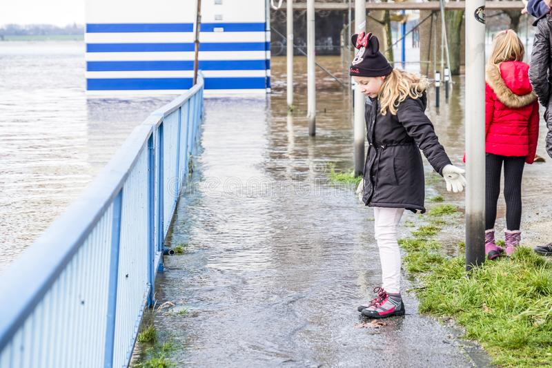 Duisburg , Germany - January 08 2017 : Little girl surprised by the river Rhine flooding the promenade. In Ruhrort stock photos
