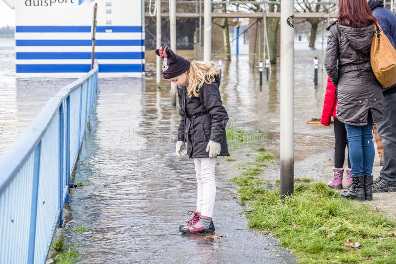 Duisburg , Germany - January 08 2017 : Little girl surprised by the river Rhine flooding the promenade. In Ruhrort stock image