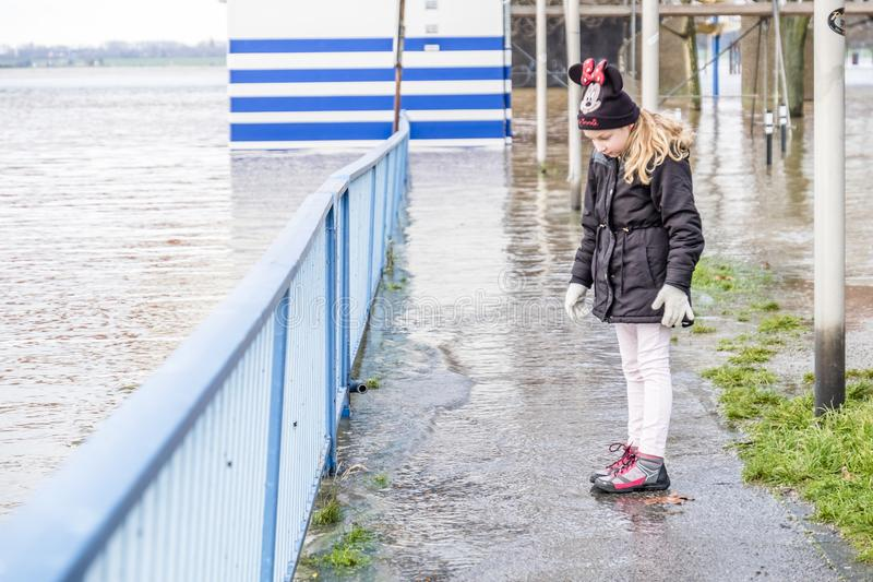 Duisburg , Germany - January 08 2017 : Little girl surprised by the river Rhine flooding the promenade. In Ruhrort royalty free stock image