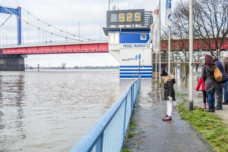 Duisburg , Germany - January 08 2017 : Little girl surprised by the river Rhine flooding the promenade. In Ruhrort royalty free stock photo