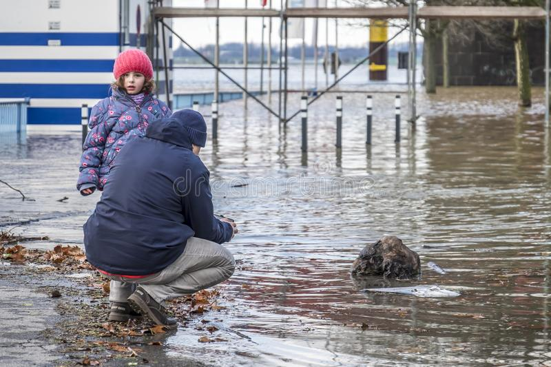 Duisburg , Germany - January 08 2017 : Man and daughter observing the the river Rhine flooding the promenade in Ruhrort. DUISBURG , GERMANY - JANUARY 08 2017 royalty free stock photos