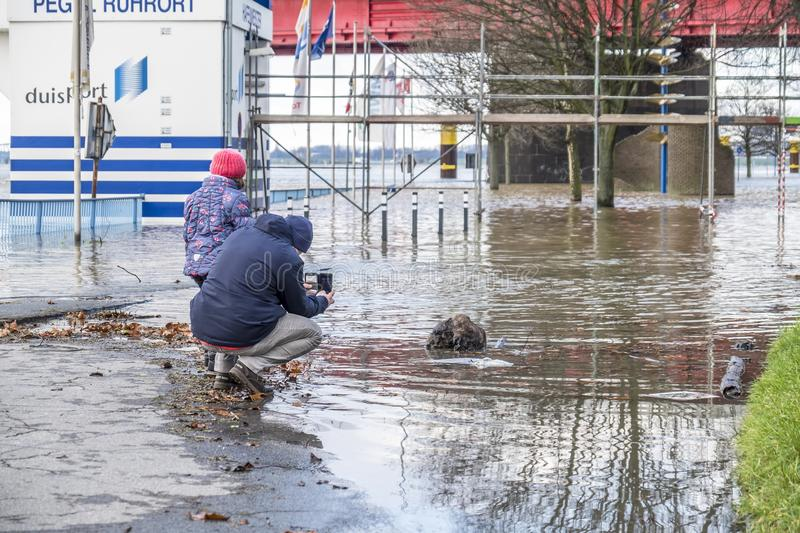 Duisburg , Germany - January 08 2017 : Man and daughter observing the the river Rhine flooding the promenade in Ruhrort. DUISBURG , GERMANY - JANUARY 08 2017 stock photos