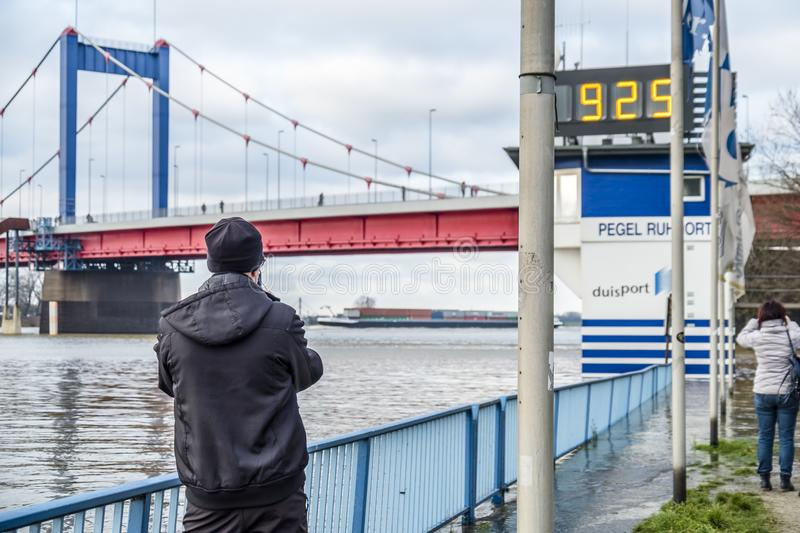 Duisburg , Germany - January 08 2017 : Tourist observing the the river Rhine flooding the promenade. In Ruhrort royalty free stock photo