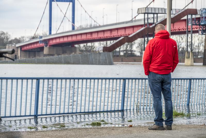 Duisburg , Germany - January 08 2017 : Tourist observing the the river Rhine flooding the promenade in Ruhrort. DUISBURG , GERMANY - JANUARY 08 2017 : Tourist royalty free stock photos