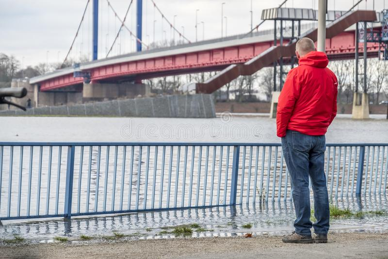 Duisburg , Germany - January 08 2017 : Tourist observing the the river Rhine flooding the promenade in Ruhrort. DUISBURG , GERMANY - JANUARY 08 2017 : Tourist royalty free stock photo