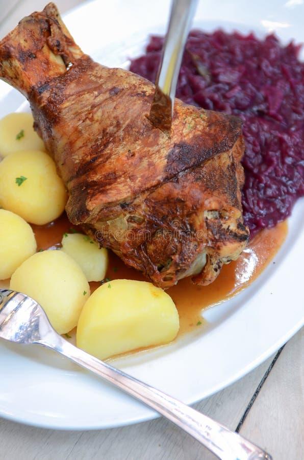 Duitse Eisbein met gesmoorde kool (Zuurkool), salade en bier, roosterde varkensvleesgewricht vraag Schweinshaxe, Beierse Haxe, stock fotografie