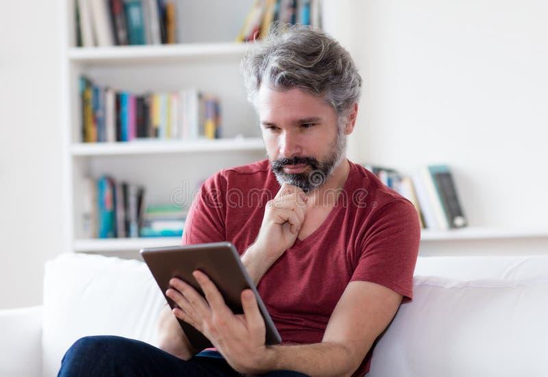 Duitse midden oude mens met de grijze e-book van de haarlezing met digitale tablet stock afbeeldingen