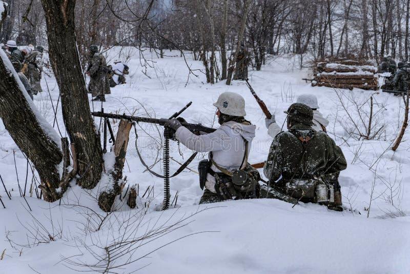 Duitse militairen met kanonnen in de winterwederopbouw van Wereldoorlog 2 stock fotografie