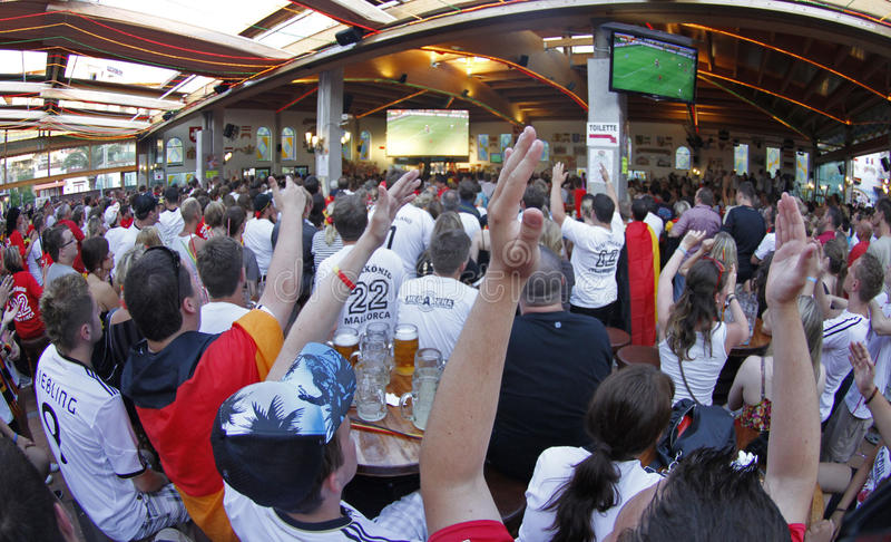 Duitse Ventilators die op de gelijke van de voetbalwereldbeker op een overvol terras letten tijdens hun vakantie in Mallorca stock foto's