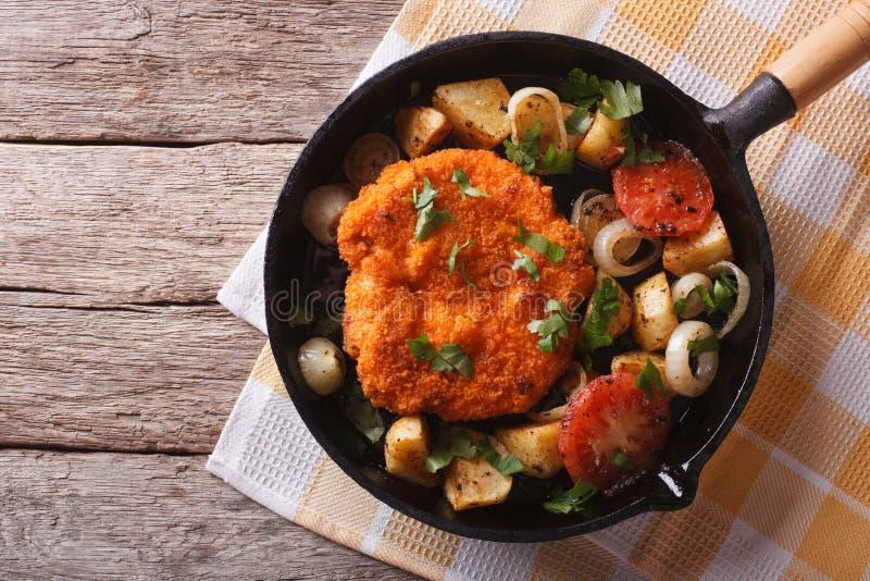 Duitse Weiner-schnitzel met groenten in een pan horizontale bovenkant stock fotografie