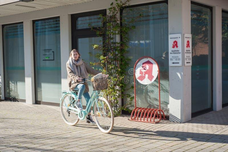 03/29/2019 Duitsland, de stad van het jonge meisje van Kamen NRW in de lente op een fiets dichtbij de stadsapotheek royalty-vrije stock afbeeldingen