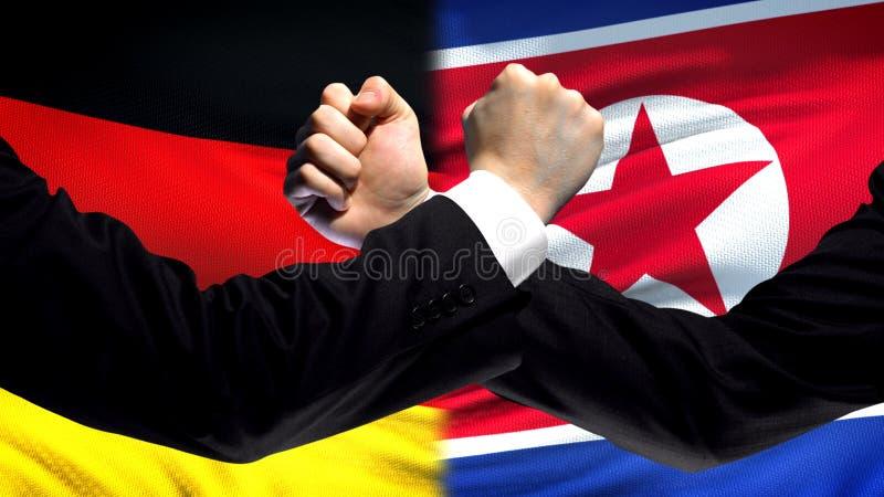 Duitsland versus de confrontatie van Noord-Korea, vuisten op vlagachtergrond, diplomatie royalty-vrije stock afbeeldingen