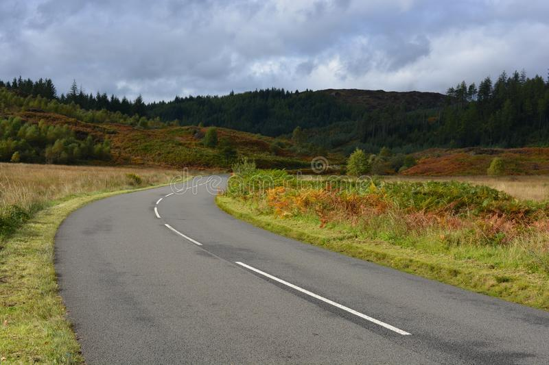 Dukes Pass, road through dramatic landscape. Diminishing perspective, the road through iconic forest landscape in the Loch Lomond and The Trossachs National Park royalty free stock photos