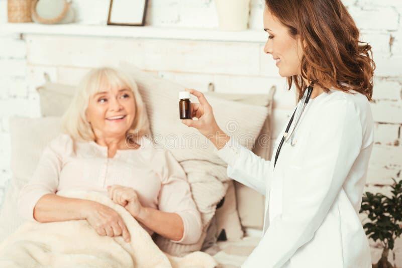 Duktig medicinsk doktor som ger medikamentet till patienten i sjukhuset arkivfoto
