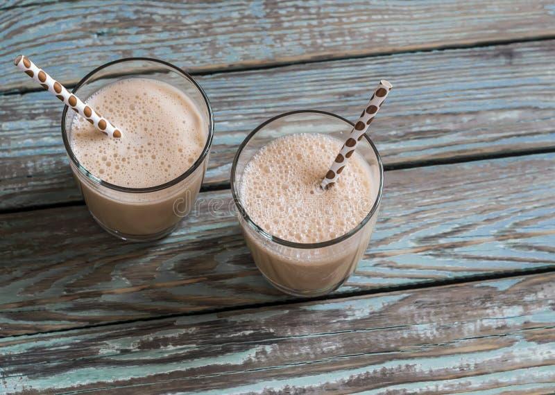 Dulce di leche och glassmilkshake i exponeringsglas på en träbakgrund arkivfoto