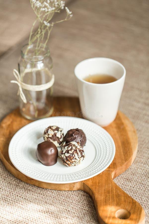 Dulces útiles con el coco en chocolate y té imagen de archivo libre de regalías