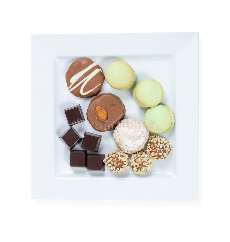 Dulces: chocolate; galletas y caramelos en una placa blanca cuadrada en el fondo blanco imágenes de archivo libres de regalías