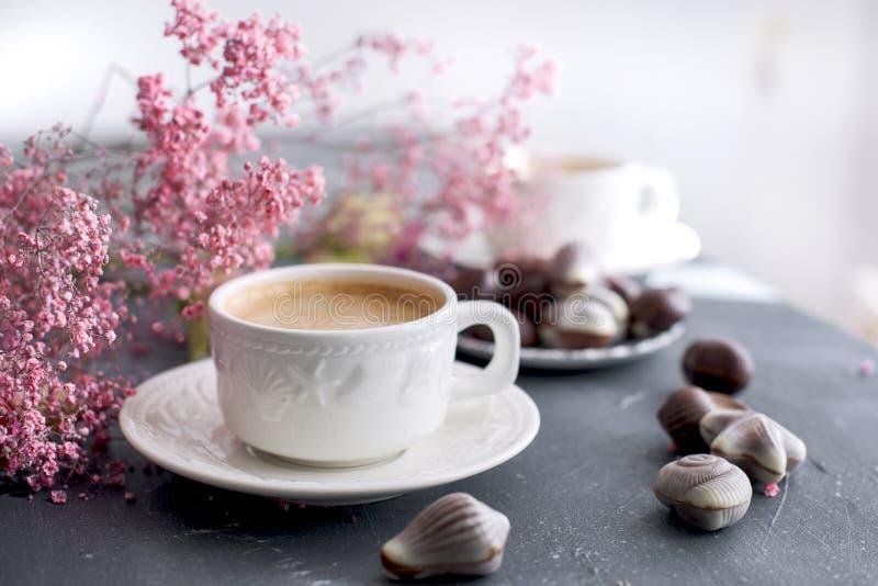 Dulces del chocolate bajo la forma de conchas de berberecho y dos tazas de café fragante Colores claros románticos del desayuno F imagen de archivo libre de regalías