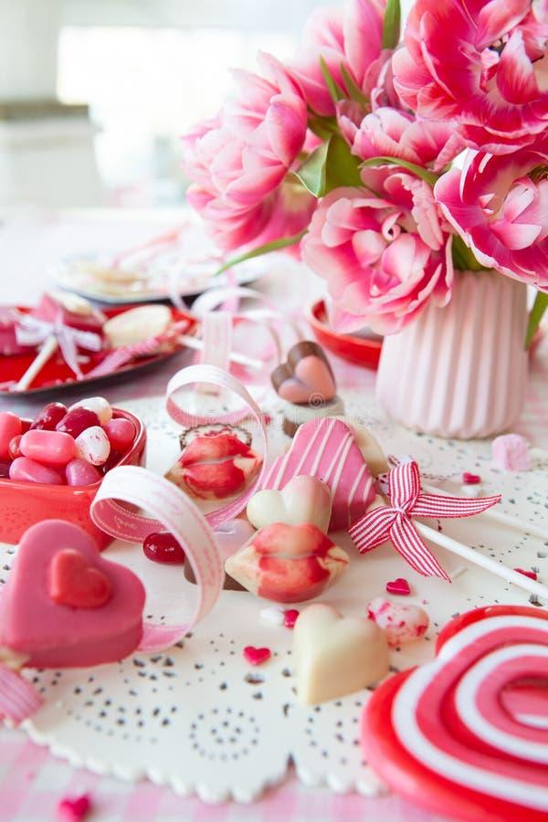 Dulces deliciosos y flores frescas imagenes de archivo