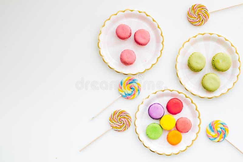 Dulces para el fondo del partido Macarons y la piruleta en la visión superior blanca copian el espacio fotos de archivo
