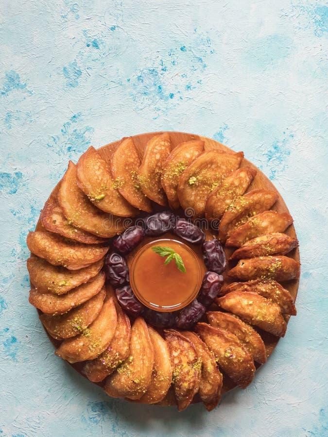 Dulces ?rabes Crepe ?rabe de Qatayef rellena con queso y nueces dulces en la tabla azul fotografía de archivo libre de regalías